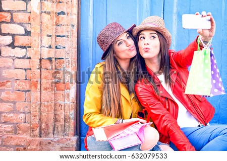 Best friends women taking selfie in funny faces holding shoppers wearing trendy fashion clothes - Girls having fun using phone camera sitting outside on old wall background - Female friendship concept #632079533