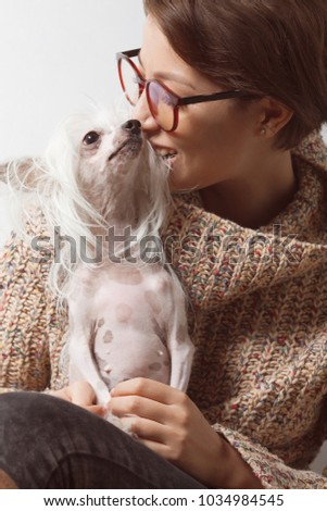 Best girlfriends concept. Young gorgeous lady with natural make-up wearing trendy clothes, eyeglasses biting ear of small dog over white background. Street fashion style. Indoor shot