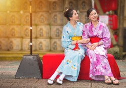 best girlfriends sitting on the culture street in Japanese festival with neat lantern background, women wearing japan traditional kimono enjoying art decoration during travel with copyspace.