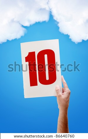 Best grade, excellent mark. White paper with number ten in male hand on blue sky background