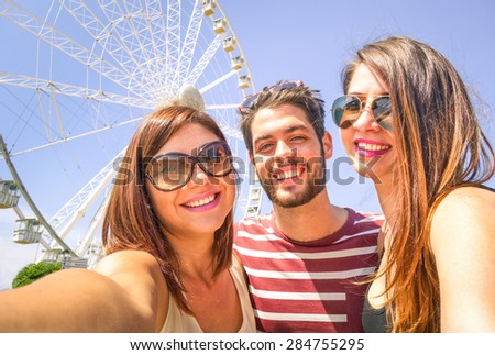 Best happy friends  with mobile taking selfie at ferris wheel - Three students at luna park - Concept of friendship and fun with new trend and technology - Young people enjoy with modern smartphone
