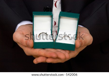best man holds two boxed wedding rings in his palms