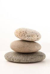best natural pebble stone on white background isolated closeup, stack of balanced zen stones, smooth sea pebbles pyramid, round yoga stones, yoga rocks heap, stacked balance cobblestone on table