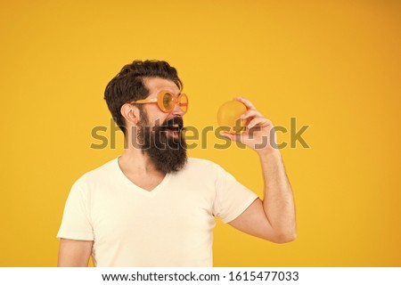 Best orange snack. Happy guy taking snack break on yellow background. Hipster looking at healthy organic snack. Snack that gives you energy, copy space.