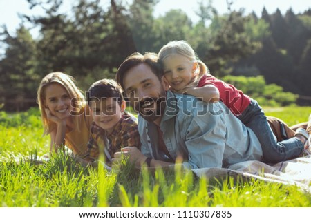 Best parents ever. Joyful bearded daddy smiling and lying on the cover with his family #1110307835
