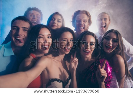 Best party mood! Close up photo portrait of couple of friends make picture, selfie on front camera of smartphone show tongue, stick out and wink eye