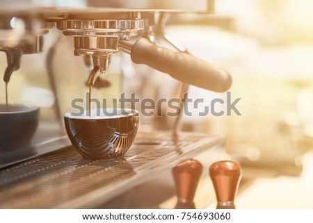 Best quality. Close up of a cup of cofffe being cooked with coffee machine in the cafe