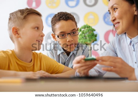 Best sample. Upbeat young teacher showing a tree model to her students and talking about the phenomenon of photosynthesis while smiling