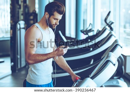 Best song for his training. Side view of young handsome man in sportswear using his smart phone while standing on treadmill at gym