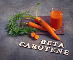 Beta carotene text and carrot juice glass