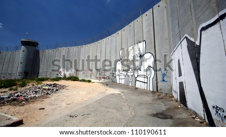 BETHLEHEM, OCCUPIED PALESTINIAN TERRITORIES - JUNE 19: Activist graffiti adorns the Israeli separation wall in the West Bank town of Bethlehem on June 19, 2011.