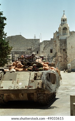 BETHLEHEM, PALESTINIAN AREAS - MAY 28: An Israeli soldier patrols the West Bank town of Bethlehem in a tank during a curfew imposed on its Palestinian residents  May 28, 2002 in Bethlehem.