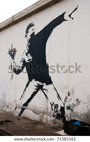 BETHLEHEM, PALESTINIAN TERRITORIES - JANUARY 25: Banksy grafitti on a wall in the occupied territories. Bethlehem, January 25, 2010. - stock photo