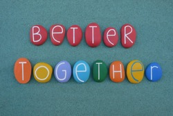 Better together, creative slogan composed with multi colored stone letters over green sand