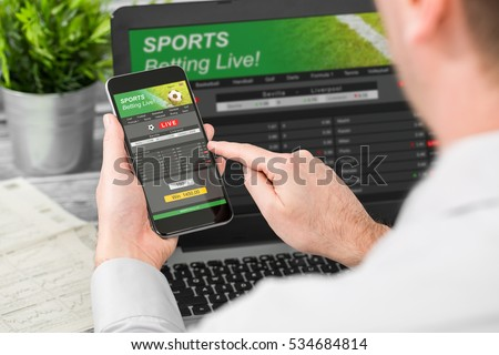 betting bet sport phone gamble laptop over shoulder soccer live home website concept - stock image Foto stock ©