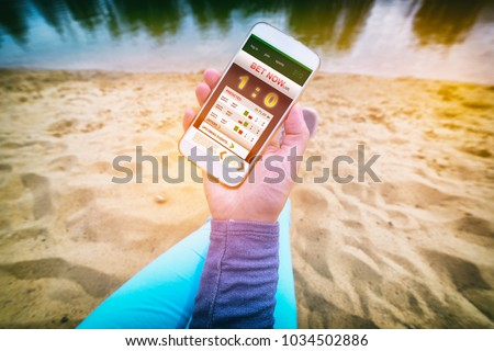 Betting on sports, hand holding smart phone with working online betting mobile application as a concept of gambling addiction