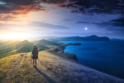 Between day and night. Girl hiker with backpack in a mountain valley. Fairytale conceptual landscape.