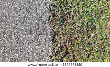 Between the road surface and the grass surface