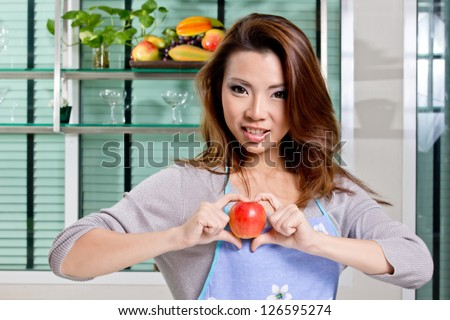 beutiful girl show apple sweet heart in kitchen (process skin tone)
