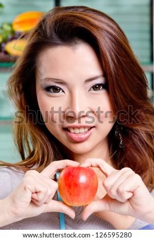 beutiful girl show apple sweet heart in kitchen (process skin tone)