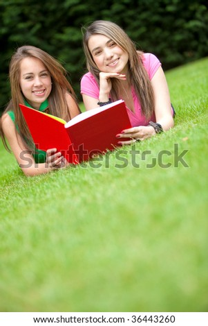 Beutiful girls reading a book outdoors and smiling