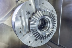 Bevel gear in a chuck on a cnc machine, machining center in production.