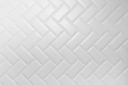 Beveled white matt ceramic tiles pattern herringbone on wall.