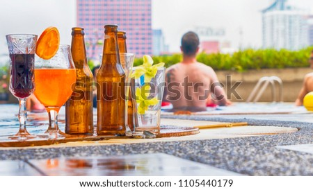 beverage and juice drink with exotic cocktails and bottle of beer set up on the swimming pool with background of people get party and swimming and blur city background