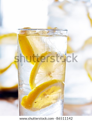 beverage- cold glass of lemonade closeup with pitcher in background