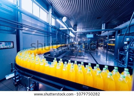 Beverage factory interior. Conveyor with bottles for juice or water. Modern equipments - Shutterstock ID 1079750282