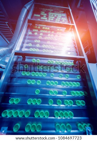 Beverage factory interior. Conveyor with bottles for juice or water. Modern equipments #1084697723