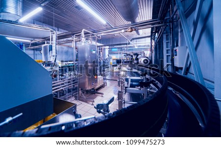 Beverage factory interior. Conveyor with bottles for juice or water. Modern equipments #1099475273