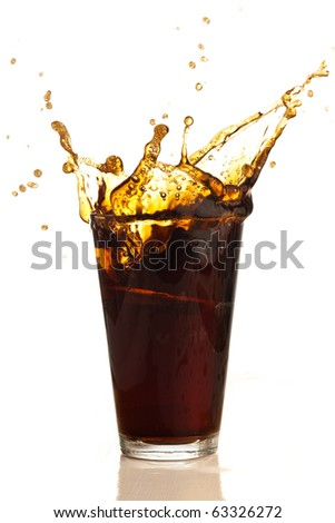 beverage splashing into glass on white background