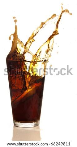 beverage splashing into glass on white background