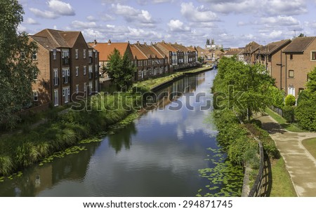 Beverley, Yorkshire, UK. The beck (canal) on a bright summer day with a view of town houses, the canal banks and footpath, and on the horizon, Beverley Minster, East Riding of Yorkshire, UK.