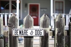 Beware of Dog sign for security on wooden fence outside of home