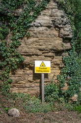 Beware of falling rock warning sign with triangle picture and alert message in yellow and black.  Stood in front of cliff face with rock on the ground.