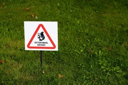 beware of squirrel sign on grass close up