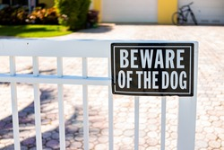 Beware of the dog sign on white fence gate railing in residential neighborhood house home in Hollywood, Florida Broward County North Miami Beach