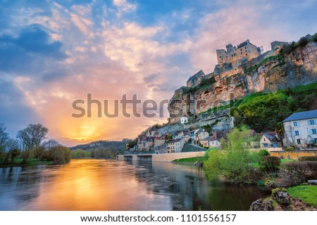 Beynac-et-Cazenac village with medieval Chateau Beynac on dramatic sunset, Dordogne, France. It is one of the most beautiful villages of France (les plus beaux villages de France)