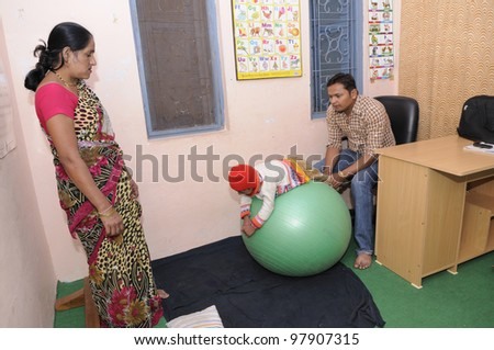 BHOPAL- DECEMBER 7:  A careful mother looks on while her daughter being treated upon for muscular problems in a rehabilitation clinic in Bhopal - India on December 7, 2010.