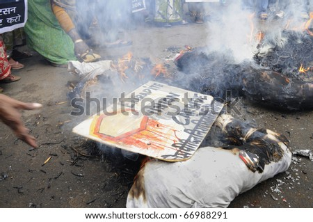 BHOPAL-DECEMBER 2: A human hand throws a placard which asks for the extradition of Warren Anderson into the burning effigy ,in Bhopal - India on December 2, 2010.