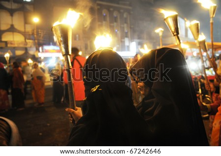 BHOPAL- DECEMBER 2: Two Muslim woman stand on the side of the road  during the torch rally organized to mark the 26th year of Bhopal gas disaster, in Bhopal - India on December 2, 2010.