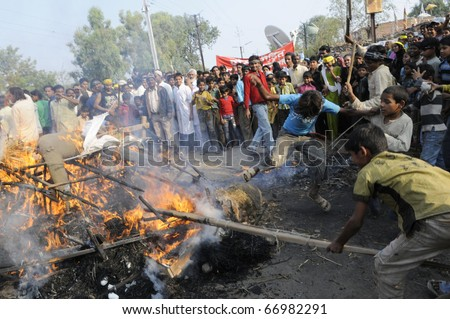 BHOPAL- DECEMBER 3: Violent youths hit the burning effigy during the rally to mark the 26th Year of the Bhopal Gas Tragedy in Bhopal - India on December 3, 2010.