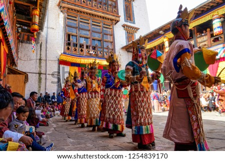 Bhutan, in Bumthang, October 19, 2018:  dancers in colourful costumes danse and play on drums on the yearly festival of Jakar while village people sitting around #1254839170