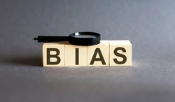 BIAS Word block fine and magnifying glass on gray background. Income, expenses, tax, financial data.