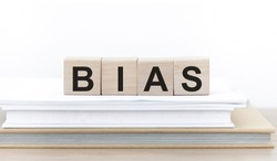 Bias - word from wooden blocks with letters, personal opinions prejudice bias concept, cubes on books