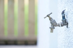 Bib tap outdoors on house external wall to water garden and car