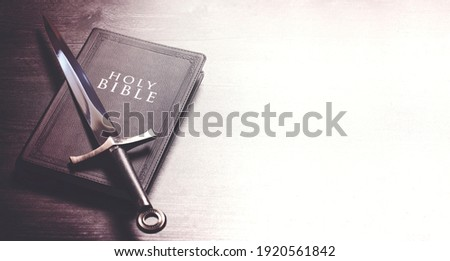 Bible and a Sword on a Dark Wooden Table Foto stock ©