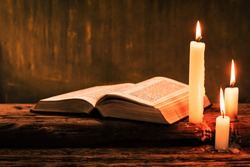 Bible and candle on a old oak wooden table.  Beautiful gold background.Religion concept.